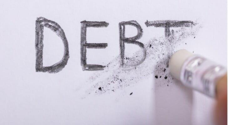 "Pencil erasing the word ""DEBT"""