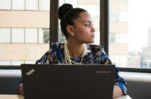 A young African American woman sits at her desk with her laptop in front of her as she looks off to the side.